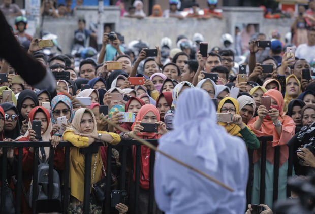 People use their mobile phones to take pictures as a Shariah law official whips a woman convicted of prostitution during a public caning outside a mosque in Banda Aceh, Indonesia, on Friday. (AP photo)
