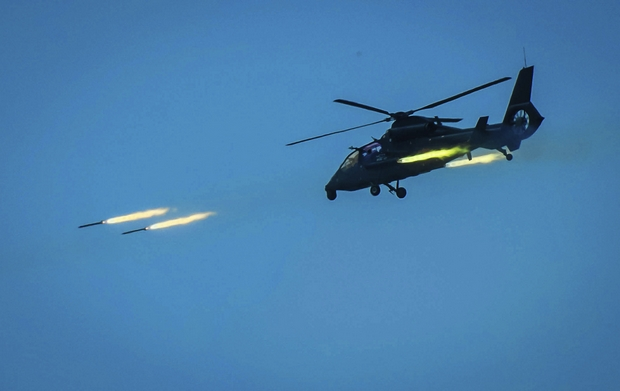 A photo provided by China's Xinhua News Agency shows a Chinese helicopter firing rockets at a target on Wednesday in a live-fire exercise off China's southeast coast. (AP Photo)