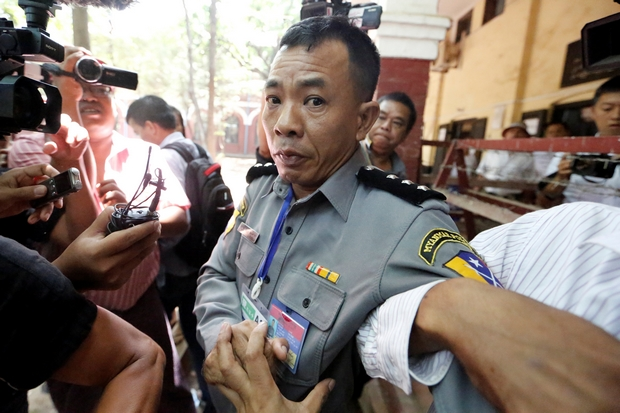 Reporters surround police captain Moe Yan Naing outside the courtroom where he testified in the trial of detained Reuters journalists Wa Lone and Kyaw Soe Oo in Yangon on Friday. (Reuters Photo)
