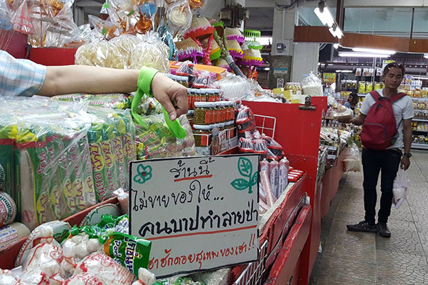 A shop in a market in Chiang Mai shows the hand of the seller with a green ribbon and a sign reading