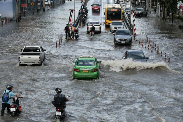 Cars and motorcycles plough through Bangkok floods. Instead of covering street space with asphalt and concrete, many cities around the world prevent flooding by planting vegetating in and around roadways. (File photo by Patipat Janthong)