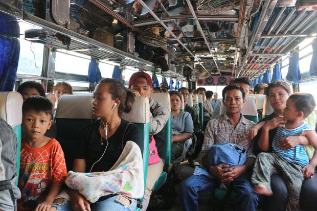 Myanmar workers board a bus in Sangkhla Buri district, Kanchanaburi, Tuesday to return to work after Songkran holidays. (Photo by Piyarach Chongcharoen)