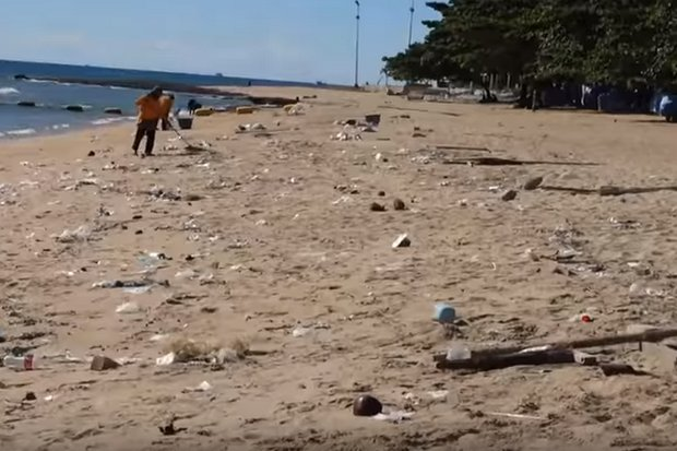 Workers constantly rake the beach and take away tonnes of trash, most of it not generated locally but washed ashore. (Screen grab YouTube/Cheap Charlie Chronicles)