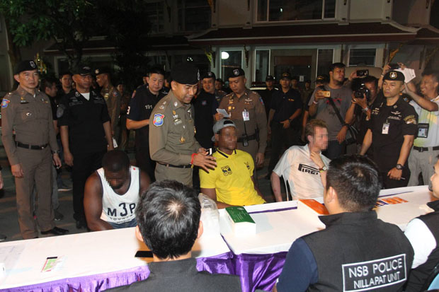 Pol Maj Gen Surachet Hakpal, deputy commissioner of tourist police, oversees the  interrogation of foreign suspects at a hotel in Bangkok, one of 118 locations raided nationwide early on Thursday. (Police photo)