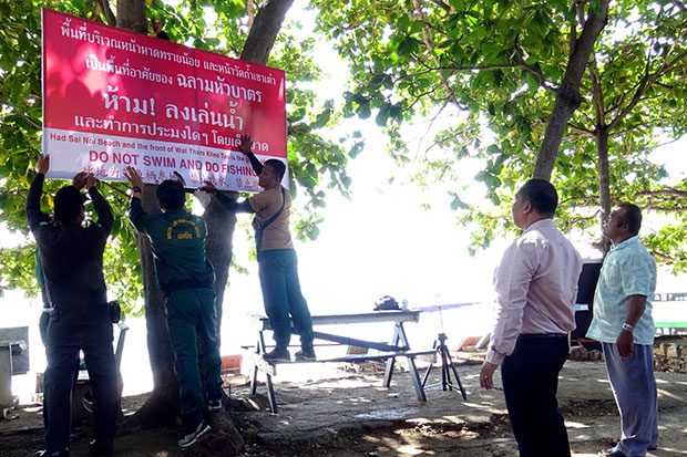 A sign is erected at Sai Noi beach in Hua Hin, Prachuap Khiri Khan, warning people not to go swimming or fishing in the sea around Wat Tham Khao, where sharks were spotted. (Photo by Chaiwat Satyaem)