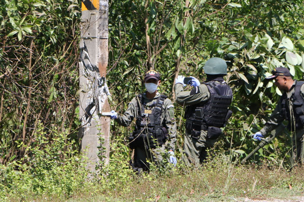 Security officers inspect a bombed electricity pole in Tak Bai district, Narathiwat, on Friday. (Photo by Waedao Harai)