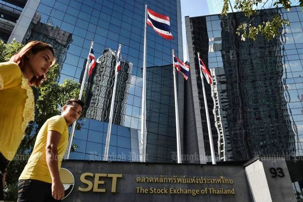Employees head for work at the Stock Exchange of Thailand (SET), as the foreign money flight has caused a downgrade in the local bourse's earnings per share. (Bangkok Post file photo)