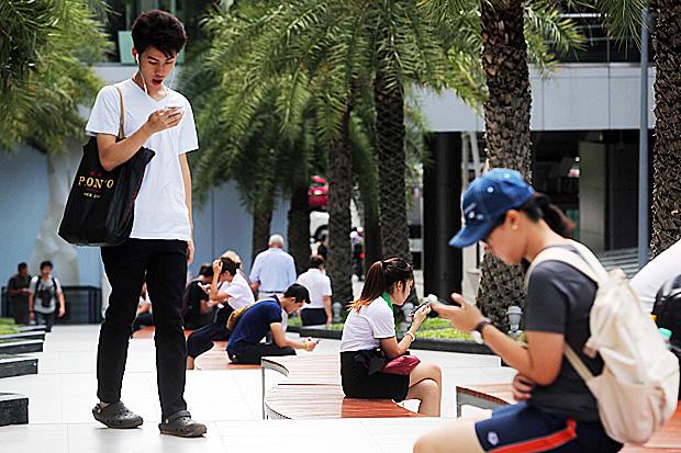 Shoppers take a mobile break at Siam Paragon. PATTARACHAI PRECHAPANICH