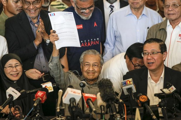 Mahathir Mohamad holds up the letter to the king that made him prime minister of Malaysia again. On the left is Azizah Wan Ismail, political ally and wife of jailed Anwar Ibrahim, who likely will be prime minister before the end of the year. (EPA photo)