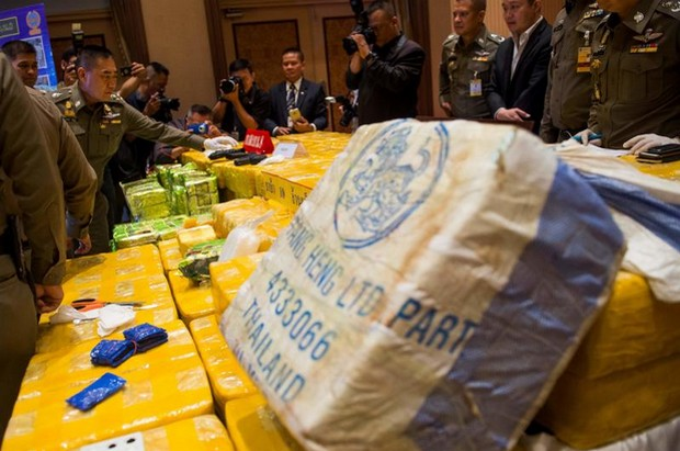 Police chief Chakthip Chaijinda, second left, inspects packages containing 10 million methamphetamine pills and nearly half a tonne of crystal meth branded as Chinese tea seized from a convoy of four vehicles in Bangkok on Thursday night, at a media briefing on Friday. (Photo AFP)