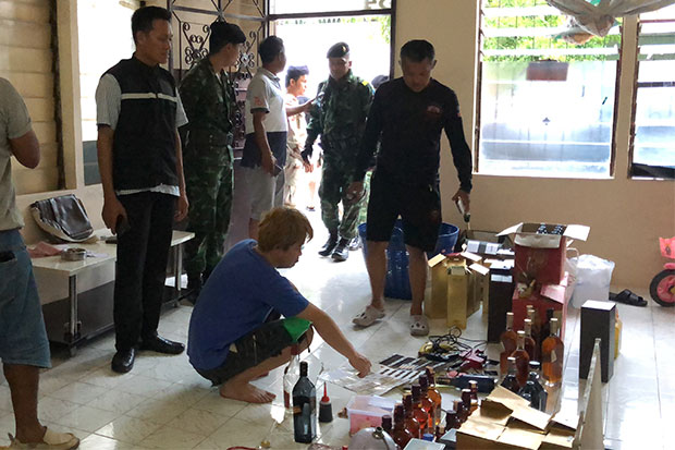 Officers gather around suspect Chan Sion Heng and a haul of liquor bottles bearing fake labels and duty stamps following his arrest in Hat Yai on Friday evening. (Photo by Assawin Pakkawan)
