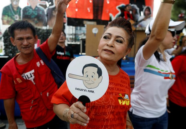 A Pro-democracy demonstrator holds a poster showing Prime Minister Prayut Chan-o-cha as Pinocchio on May 5. The demonstrators called for a general election this year. (Reuters photo)