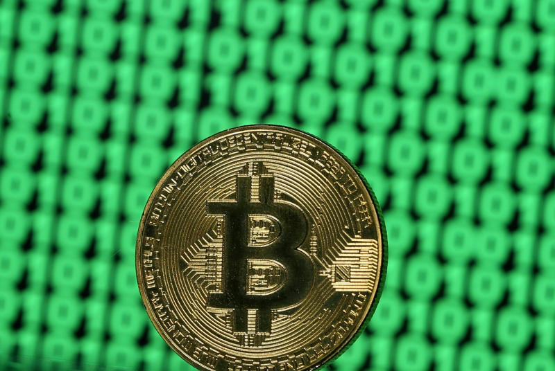 A token of the virtual currency Bitcoin is seen placed on a monitor that displays binary digits. (Reuters file photo)