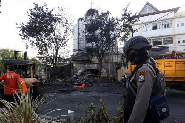 The body of a suicide bomber lies  under an orange covering (background) as police secure the site of a terrorist attack on one of several churches bombed on Sunday in Surabaya. (AP photo)