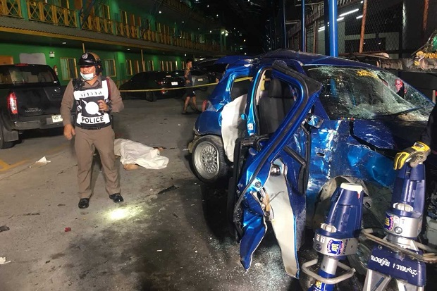 A policeman stands guard at the crash site after the victims had bee pulled out of the wrecked sedan.(photo by Chaiyot Pupattanapong)