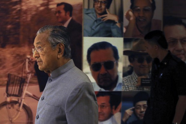 New Malaysian Prime Minister Mahathir Mohamad walks by a board displaying his photos after a news conference in Putrajaya on Monday. (AP photo)