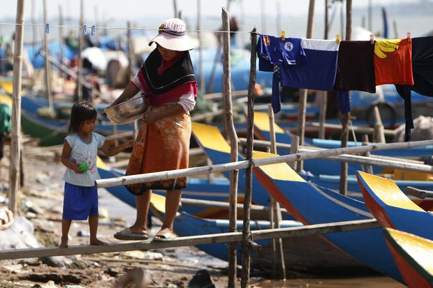 A woman walks with her child at the fishermen's village of Kbal Chroy on the Mekong River bank near Phnom Penh on Thursday.(AP photo)
