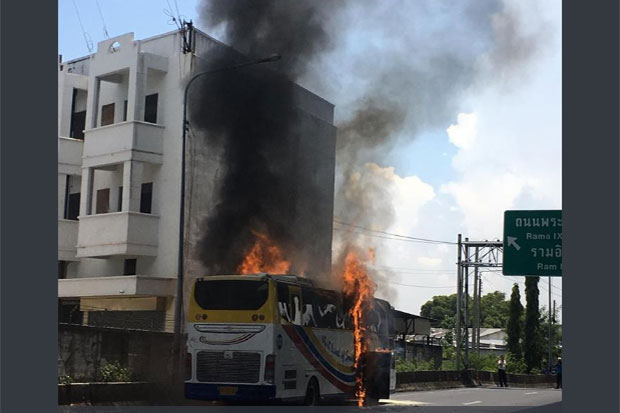 A tour bus catches fire shortly after entering an expressway in Phra Khanong district of Bangkok on Saturday afternoon, forcing more than 30 tourists to flee. (Photo from @fm91trafficpro Facebook page)