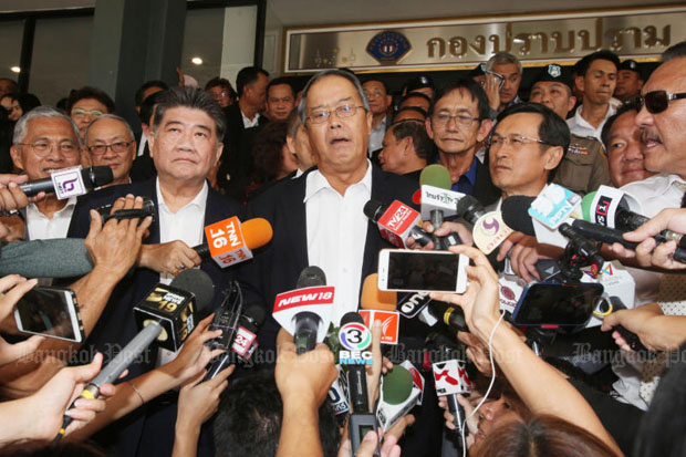 Chusak Sirinil (centre) and other key Pheu Thai Party members speak to reporters at the Crime Suppression Division in Bangkok on Monday. (Photo by Apichit Jinakul)