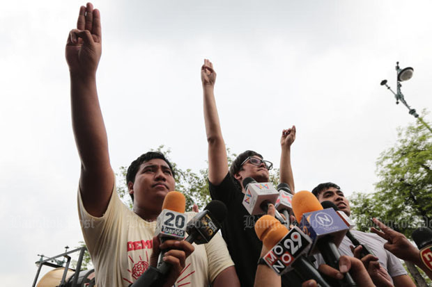 From left, rally leaders Sirawit Serithiwat, Rangsiman Rome and Piyarat Jongthep offer a three-finger salute as they announce the end of their pro-election demonstration and surrender to police in front of Thammasat University in Bangkok on Tuesday afternoon. (Photo by Wichan Charoenkiatpakul)