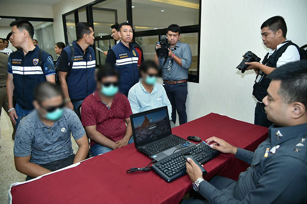A police officer questions three Indian suspects about their alleged roles in a scam that used the names of hundreds of women in Sara Buri in forged marriage certificates. (Photo from Tourist Police Bureau)
