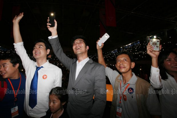 Thanathorn Juangroongruangkit (centre) and supporters  hold up their mobile phone flashlights to symbolise a bright political future, after Anakhot Mai (Future Forward) Party members selected him as party leader at a meeting Sunday at Thammasat University's Rangsit campus. (Photo by Apichit Jinakul)