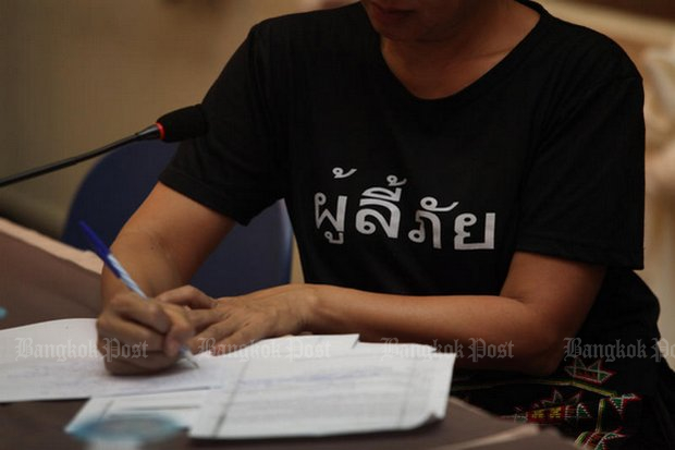 A participant wearing a T-shirt emblazoned with 'Refugees' makes a note at a forum on the condition of refugees along Thai borders in Jan this year. (Photo by Thiti Wannamontha)