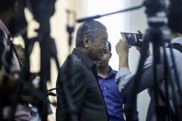 Malaysian Prime Minister Mahathir Mohamad (centre) arrives at a press conference in Kuala Lumpur on Monday. (EPA-EFE photo)