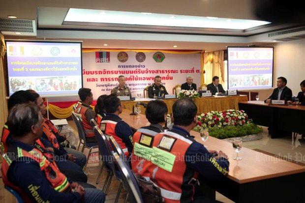Drivers from the app-controlled Grab motorcycle-taxi service listen as officials from the army and Department of Land Transport outline new regulations. (Photo by Apichart Jinakul)