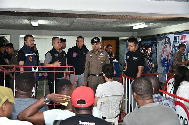 Pol Maj Gen Surachate Hakparn, deputy chief of the Tourist Police Bureau, centre, interrogates some of the 42 foreign suspects rounded up during coordinated raids on 83 locations nationwide on May 31. (Photo supplied by the Tourist Police Bureau)