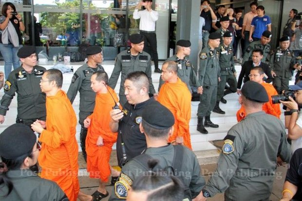 Senior monks and assistants are directed to court last week through a gauntlet of elite policemen who raided their temples. (Post Today photo)