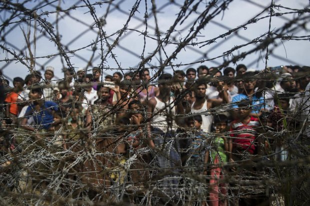 This April 25 picture taken from Maungdaw district, Myanmar's Rakhine state shows Rohingya refugees gather April 25 in a barbed-wire enclosure at a temporary settlement in a 'no man's land' border zone opposite Maungdaw district of Myanmar. (AFP photo)