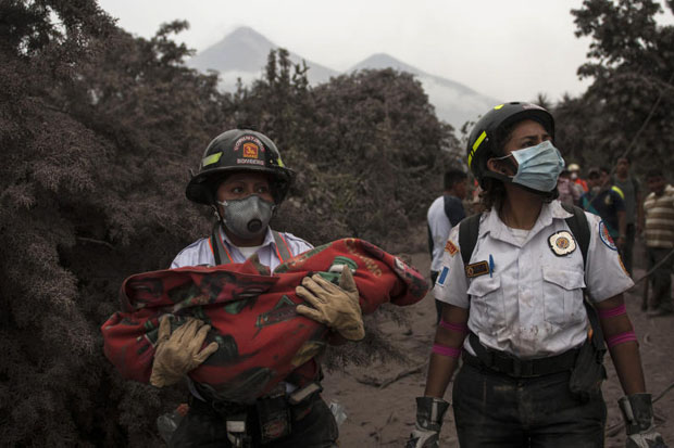 A firefighter carries the body of a child recovered near the Volcan de Fuego, which means in Spanish Volcano of Fire, in Escuintla, Guatemala, Monday. A fiery volcanic eruption in south-central Guatemala sent lava flowing into rural communities, killing dozens. (AP photo)