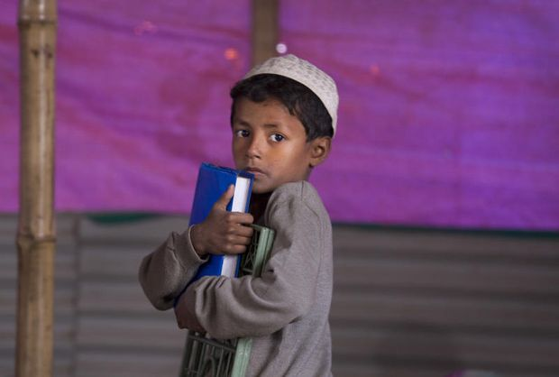 A Rohingya refugee boy holds his books as he leaves a makeshift school in a Mosque at Balukhali refugee camp near Cox's Bazar, Bangladesh, on Jan 17, 2018.