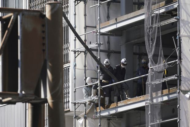 In this March 22 photo, workers adjust a hose at a construction site in Tokyo. (AP photo)