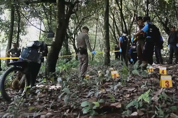 Police and forensic officers on Friday inspect the scene of the fatal shooting of four gold panners at a rubber plantation in Sukhirin district, Narathiwat on Thursday night. (Photo by Waedao Harai)