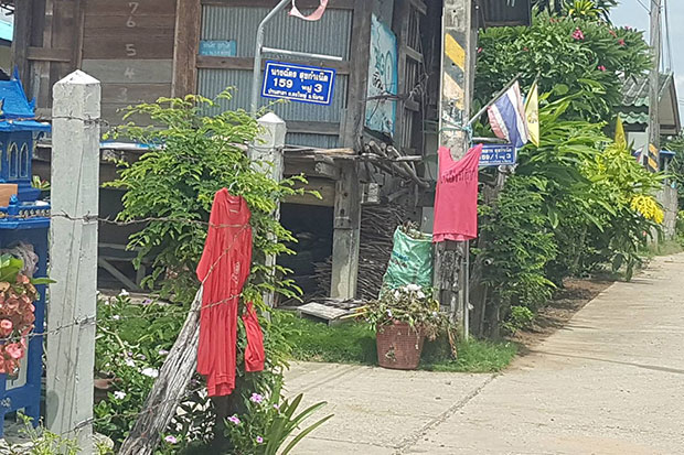 Villagers of Ban Sala in Phimai district in Nakhon Ratchasima hang red shirts to drive away the ghost of a widow believed to have taken the lives of two males in the village. (Photo by Prasit Tangprasert)