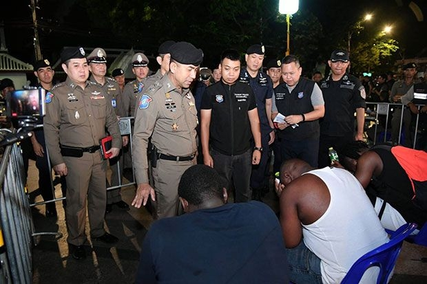 Tourist Police Bureau deputy chief Pol Maj Gen Surachate Hakparn, flanked by members of the arresting team, interrogate some of the foreigners arrested for visa breaches and other offences early Saturday. (Photo supplied by Tourist Police Bureau)
