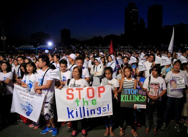 Participants display placards as they participate in a procession against plans to reimpose death penalty and intensify drug war during