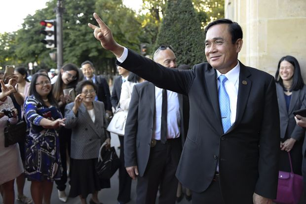 Prime Minister Prayut Chan-o-cha flashes an 'I Love You' sign to well-wishers in front of his hotel in Paris on Saturday. (Royal Thai Government photo)