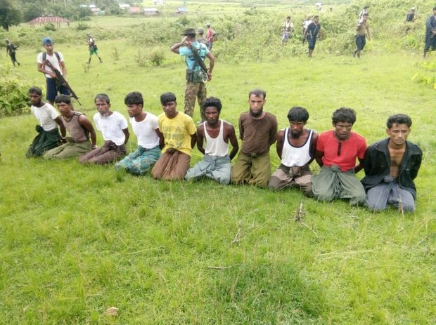 Ten Rohingya Muslim men with their hands bound kneel before being executed as members of the Myanmar security forces stand guard in Inn Din village Sept 2, 2017. (Reuters file photo)