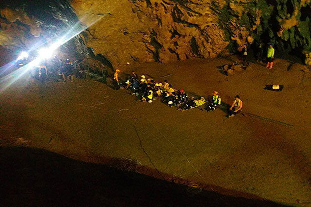 Rescuers rest outside the cave in the Tham Luang Khun Nam Nang Non Forest Park in Mae Sai district, Chiang Rai, on Monday during a search of 12 boys and their football coach trapped inside. (Photo by Channaphat Chaimol)