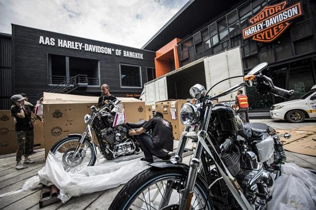 Workers unpack new motorcycles arriving at a Harley-Davidson showroom in Bangkok on May 15. (New York Times photo)