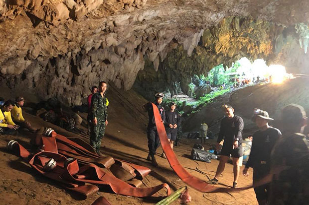Navy Seal divers and rescuers carry hoses for electric pumps into flooded Tham Luang cave as the search continues for the missing footballers in Chiang Rai province. (Photo by @ThaiSEAL Facebook page)