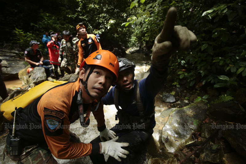 Rescuers climb a mountain above Tham Luang cave in Mae Sai district, Chiang Rai, trying to other openings into the cave to search for 12 boys and their football coach missing there Wednesday. (Photo by Patipat Janthong)