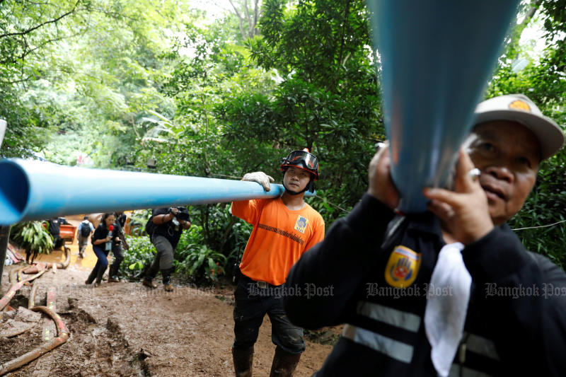 Soldiers and rescue workers carry water pipes to Tham Luang cave during a search for members of a youth football team and their coach in Mae Sai district, Chiang Rai, on Thursday. (Reuters photo)