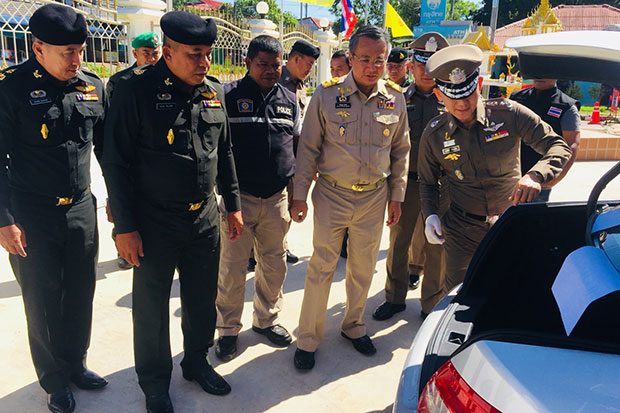 Pol Lt Gen Sorasak Yenprem, commander of Provincial Police Region 8, right, shows Surat Thani governor Witchawut Jinto, second right, the compartment in the back of the Mercedes-Benz where the 506,000 methamphetamine pills were hidden. (Photo by Supapong Chaolan)