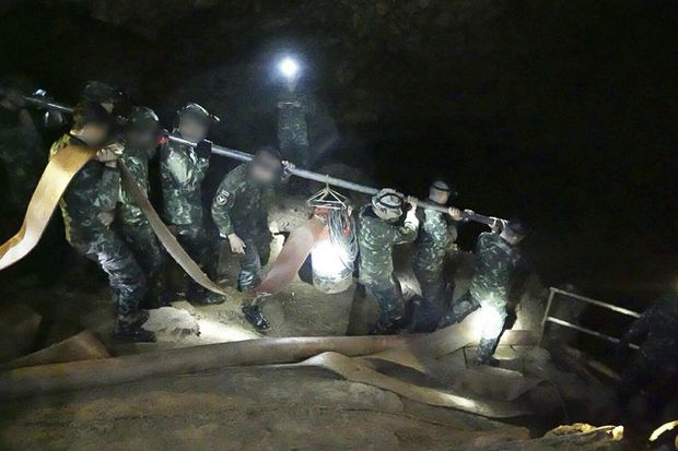 Navy Seals and soldiers carry another water pump into Tham Luang cave to accelerate drainage on Saturday. (Photo courtesy of Thai Navy Seals)