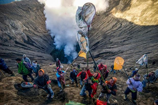 People prepare to catch offerings thrown by Tengger tribe people into the crater of Bromo volcano to in Probolinggo, East Java province, on Saturday as part of Yadnya Kasada festival, which falls on the 14th day of the Kasada month based on the traditional Hindu lunar calendar. (AFP PHOTO)