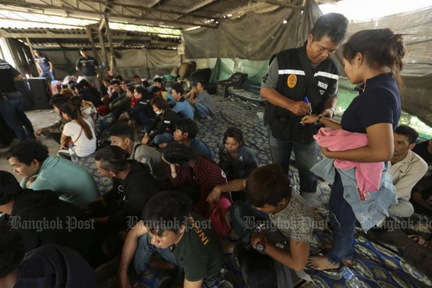 In this file photo from last year, police check identities of Cambodian migrants. A new operation begins this week to round up and deport thousands of unregistered migrants from nearby countries. (Photo by Patipat Janthong)
